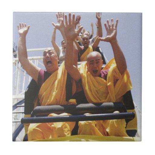 Monjes budistas felices en una montaña rusa teja  ceramica