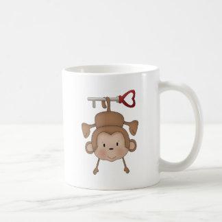 Monkey hanging on heart key coffee mug