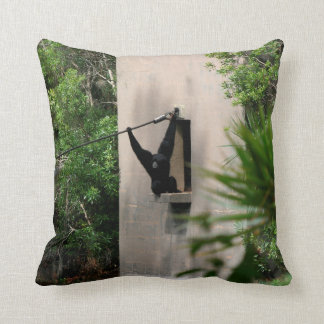 monkey hanging out of concrete house window throw pillow