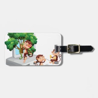 Monkeys playing and eating on computer screen luggage tag