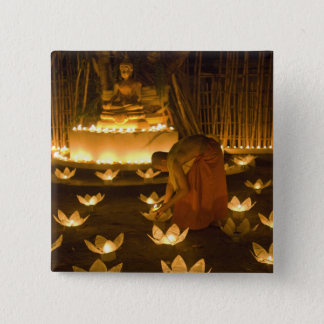 Monks lighting khom loy candles and lanterns for button