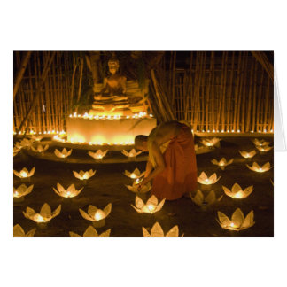 Monks lighting khom loy candles and lanterns for card