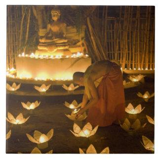 Monks lighting khom loy candles and lanterns for ceramic tile