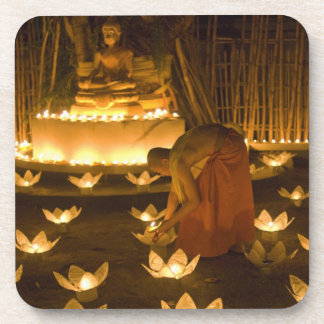 Monks lighting khom loy candles and lanterns for coasters