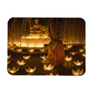 Monks lighting khom loy candles and lanterns for magnet
