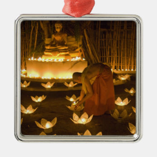 Monks lighting khom loy candles and lanterns for metal ornament