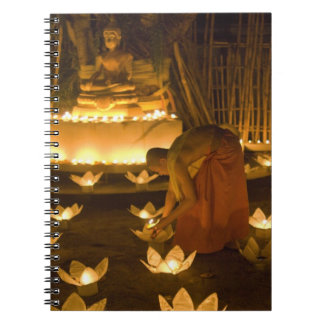Monks lighting khom loy candles and lanterns for notebook