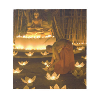 Monks lighting khom loy candles and lanterns for notepad
