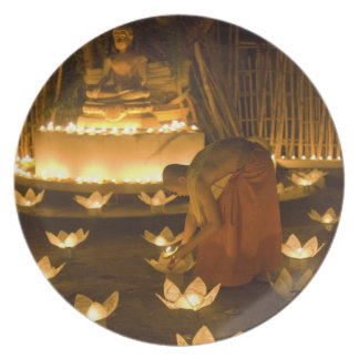 Monks lighting khom loy candles and lanterns for dinner plates
