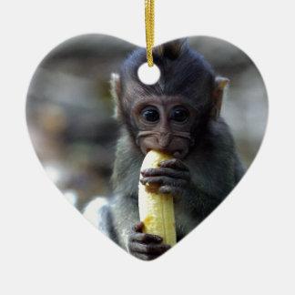Mono de macaque lindo del bebé que come el plátano adorno navideño de cerámica en forma de corazón