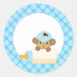 Mono del bebé detrás de la botella etiqueta redonda