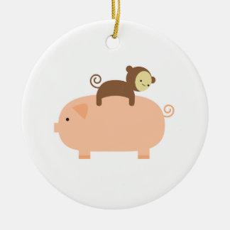 Mono del bebé que monta al revés en un cerdo adorno navideño redondo de cerámica