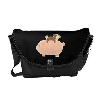 Mono del bebé que monta al revés en un cerdo bolsa messenger