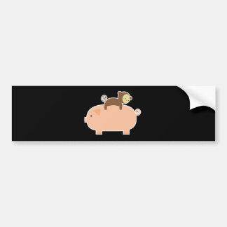 Mono del bebé que monta al revés en un cerdo etiqueta de parachoque