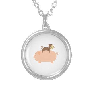 Mono del bebé que monta al revés en un cerdo colgante redondo