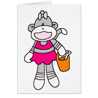 Mono del calcetín del chica en la playa felicitacion