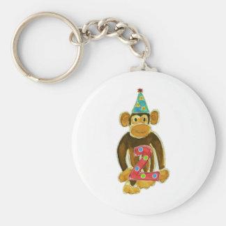 Mono del cumpleaños que sostiene dos llavero redondo tipo pin