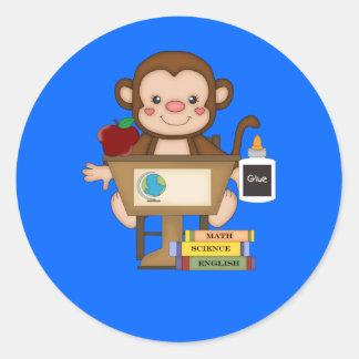 Mono en la escuela que se sienta en el escritorio etiquetas redondas