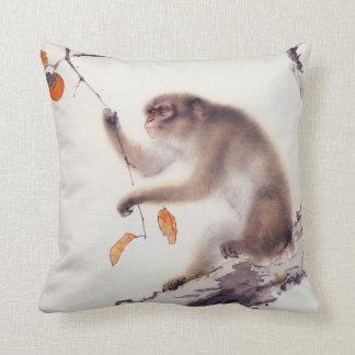 Mono en un árbol de caqui cojín