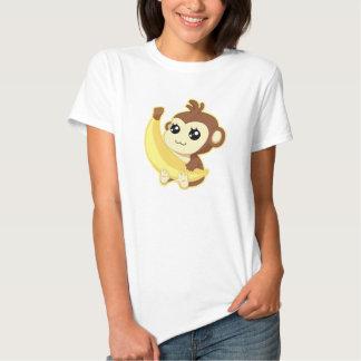 Mono lindo de Kawaii que sostiene el plátano Remeras