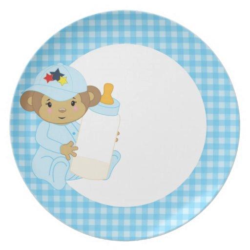 Mono lindo del bebé azul que sostiene una botella plato