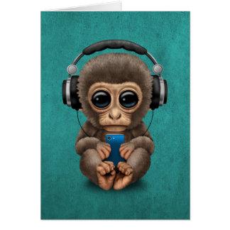 Mono lindo del bebé con el auricular que lleva del tarjeta pequeña
