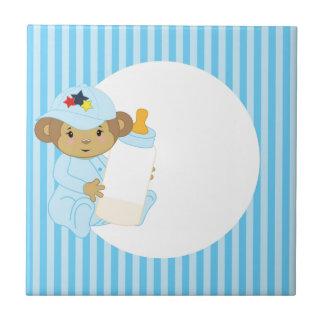 Mono lindo del bebé del muchacho que sostiene una  azulejo cuadrado pequeño