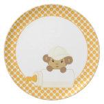 Mono lindo del bebé detrás de una botella en amari plato para fiesta