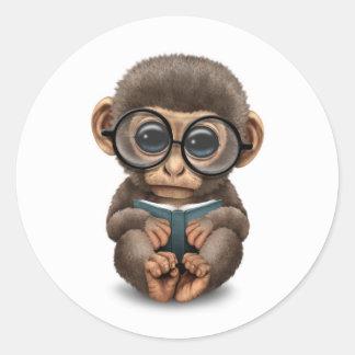 Mono lindo del bebé que lee un libro en blanco etiquetas redondas