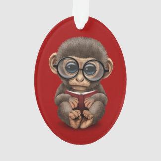 Mono lindo del bebé que lee un libro en rojo