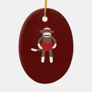 Mono lindo del calcetín con el gorra que lleva a adorno navideño ovalado de cerámica