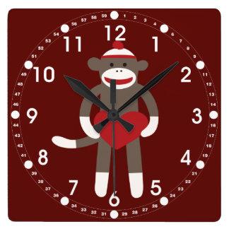 Mono lindo del calcetín con el gorra que lleva a c relojes