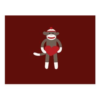 Mono lindo del calcetín con el gorra que lleva a c tarjetas postales