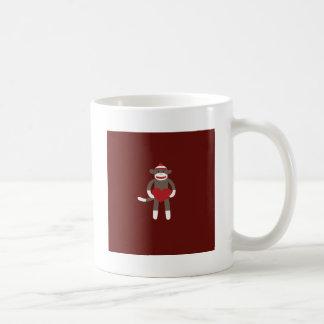 Mono lindo del calcetín con el gorra que lleva a c taza