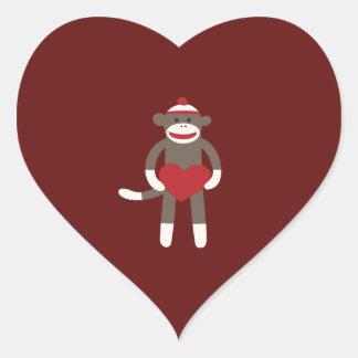 Mono lindo del calcetín con el gorra que lleva a pegatina en forma de corazón