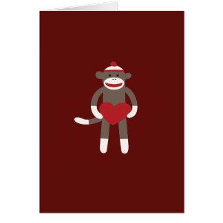 Mono lindo del calcetín con el gorra que lleva a tarjeton