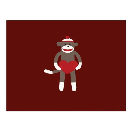 Mono lindo del calcetín con el gorra que lleva a tarjetas postales