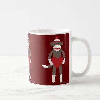 Mono lindo del calcetín con el gorra que lleva a taza de café