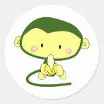 Mono lindo del dibujo animado que come un plátano etiquetas redondas