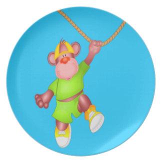 Mono lindo del dibujo animado que cuelga de una vi plato