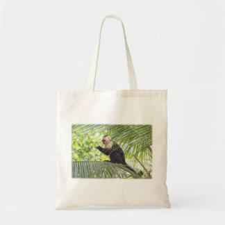 Mono lindo en una palmera bolsa de mano