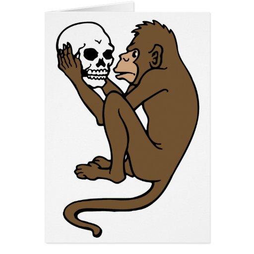 Mono que sostiene un cráneo felicitación
