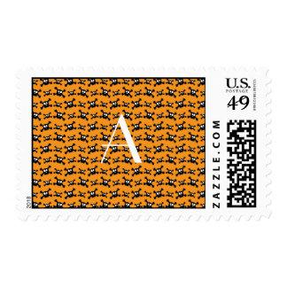 Monogram orange skulls pattern postage stamps