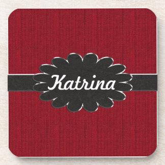 Monograma de cuero negro en fondo material rojo posavasos de bebida