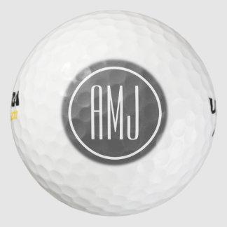 Monograma de los gris plateados y del blanco del pack de pelotas de golf
