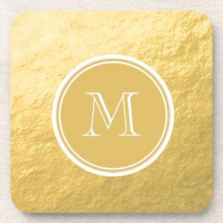 Monograma del fondo de la hoja de oro del encanto posavasos de bebida