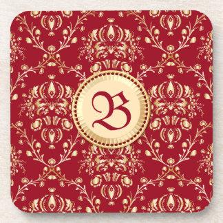 Monograma medieval magnífico del rojo del carmín posavasos