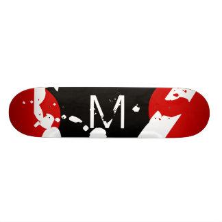 Monopatín rojo, negro y blanco de la pintada del m