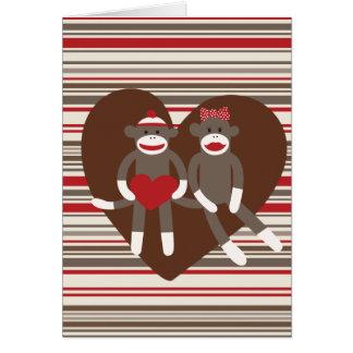 Monos del calcetín en regalos del corazón del el tarjeta de felicitación