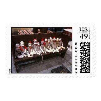 Monos del calcetín en un banco estampillas